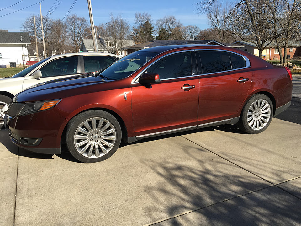 wine colored four door car with window tinting
