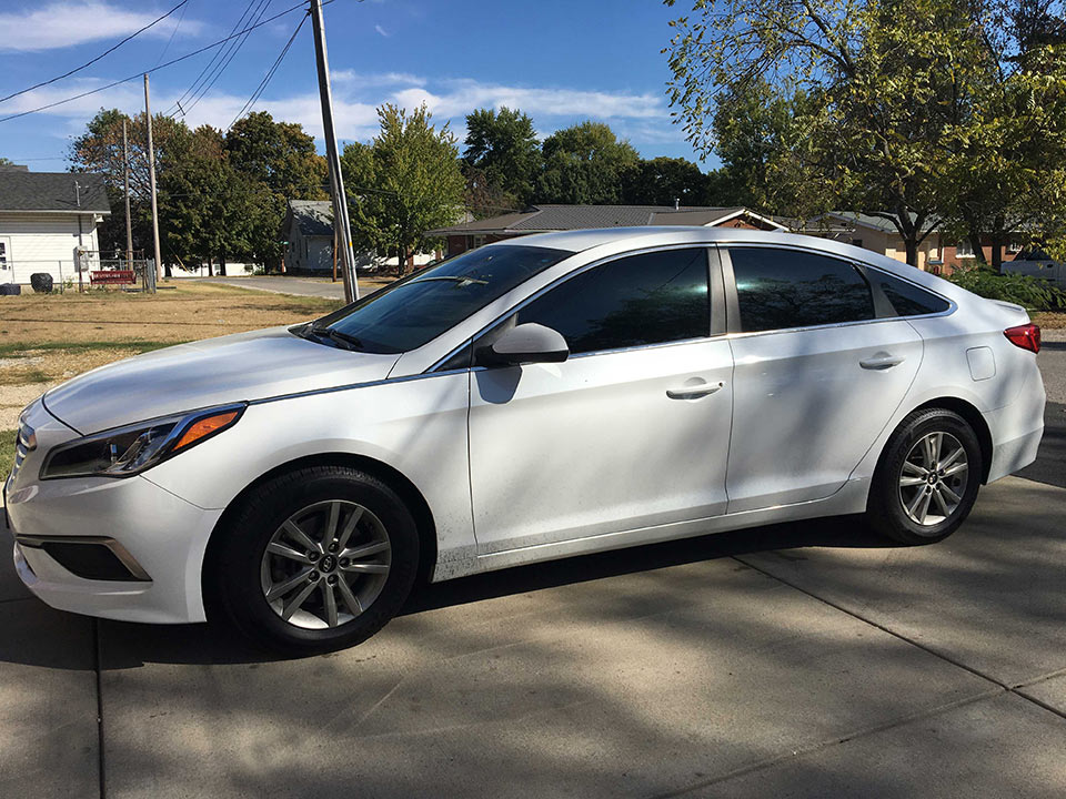 white four door car with automotive window tinting